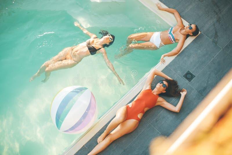 Tre unga kvinnor som kopplar av i simbassängen arkivbilder