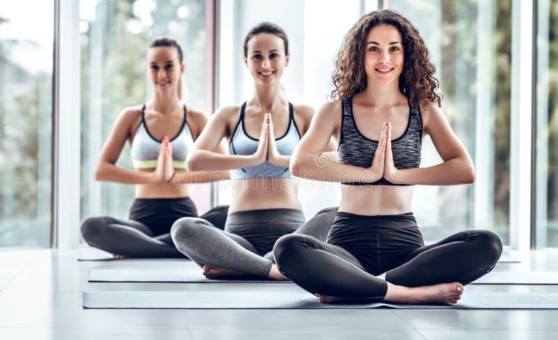 Tre unga kvinnor som kopplar av och mediterar under deras yogagrupp i en idrottshall royaltyfri fotografi