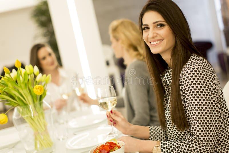 Tre unga kvinnor som rostar med vitt vin fotografering för bildbyråer