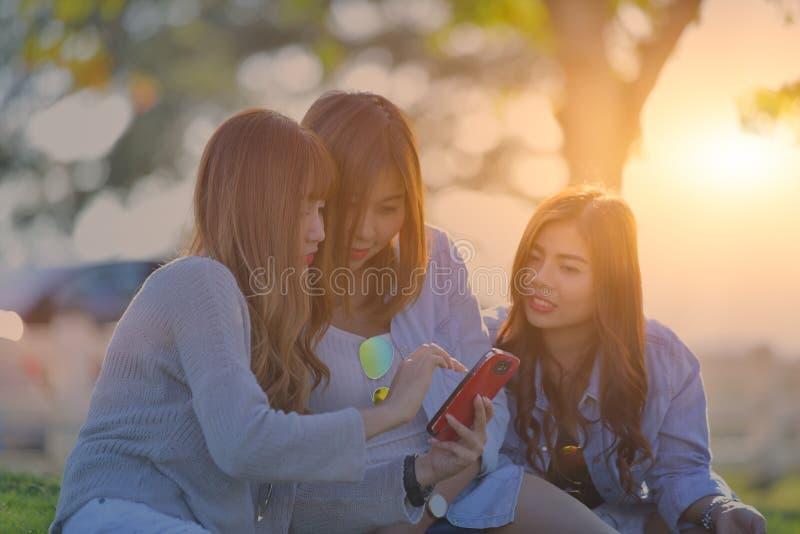 Tre unga kvinnor som ser i mobiltelefon Tonåriga flickor för bylte Outd arkivbilder