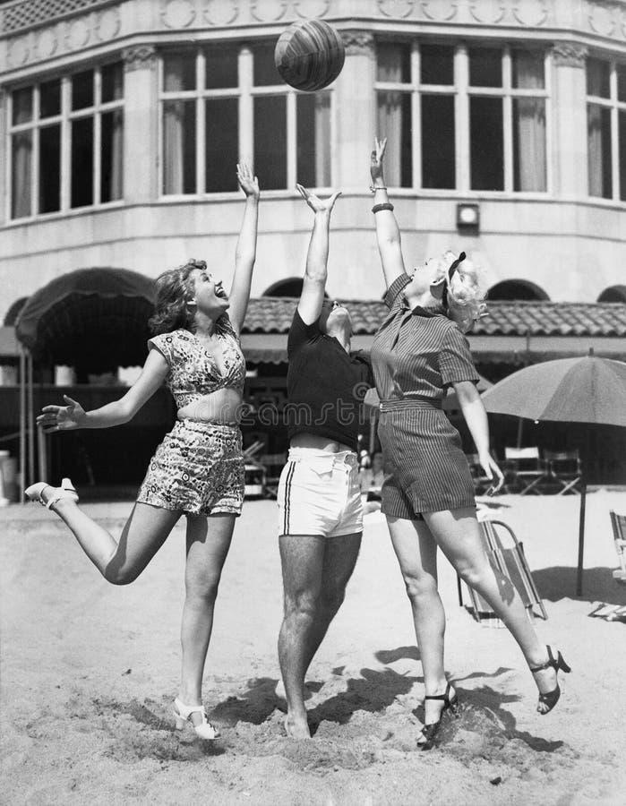 Tre unga kvinnor som spelar med en boll på stranden (alla visade personer inte är längre uppehälle, och inget gods finns Leverant arkivfoton