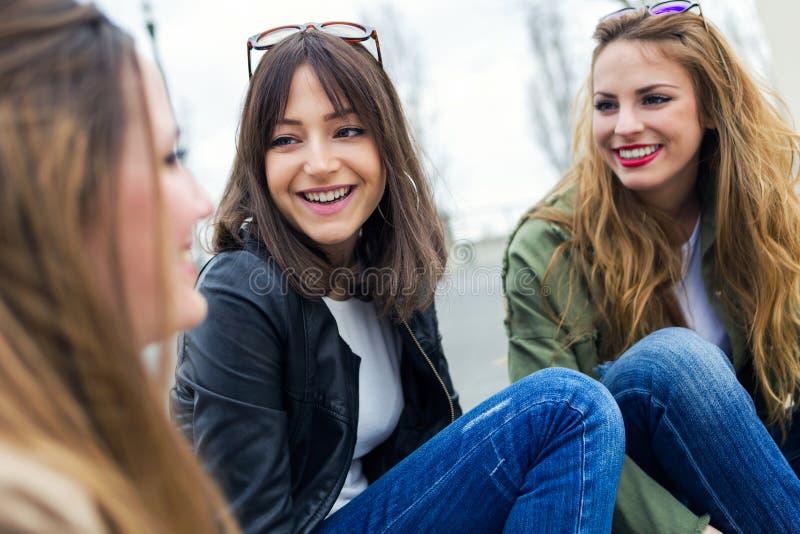 Tre unga kvinnor som talar och skrattar i gatan royaltyfria foton