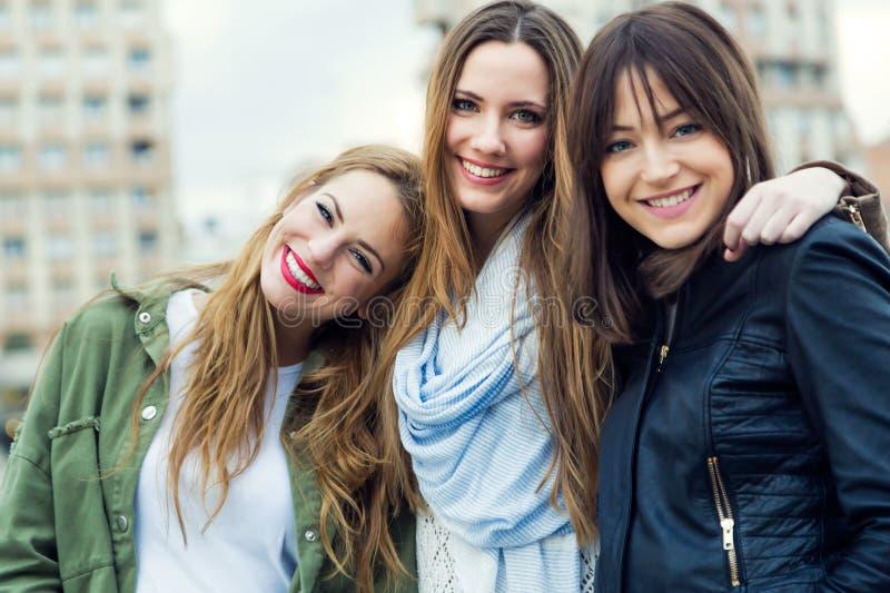 Tre unga kvinnor som talar och skrattar i gatan royaltyfri bild