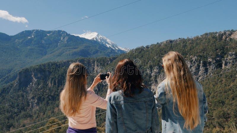 Tre unga kvinnor som tar selfie med mobiltelefonen royaltyfri fotografi