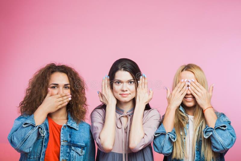 Tre unga kvinnor som tre kloka apor Muta döv rullgardin royaltyfri foto