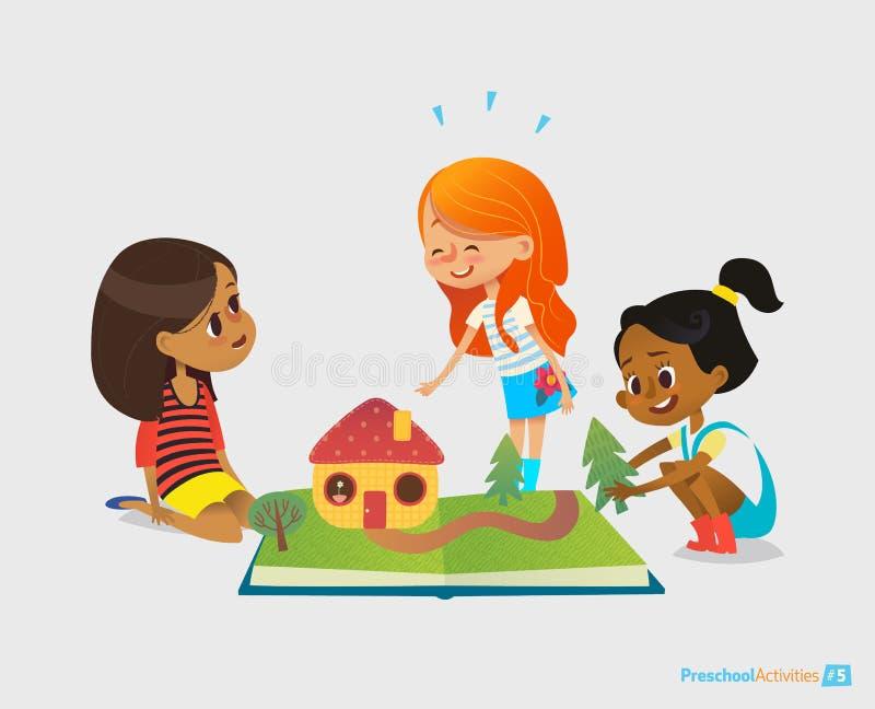 Tre unga le flickor sitter på golv, talar och spelar med pop-uppboken Underhållning och förträning för barn` s royaltyfri illustrationer