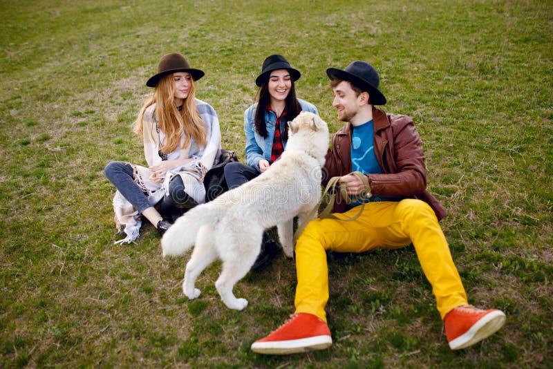 Tre unga lyckahipstervänner som talar på grönt gräs och deras skrovliga hund royaltyfria foton