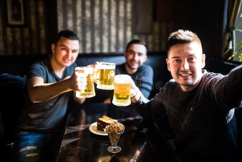 Tre unga män i tillfällig kläder ler, tar selfie och dricker öl, medan sitta i bar barnfadergyckel som har att leka tillsammans arkivfoton