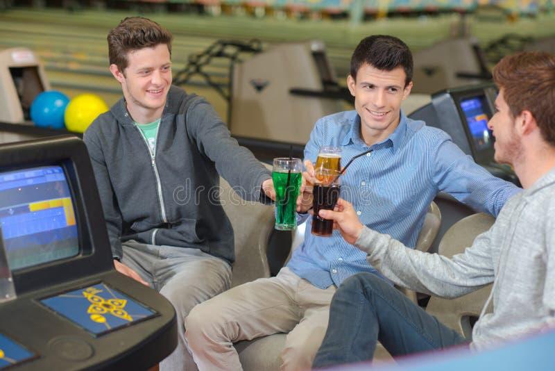 Tre unga män på bowlingbanan som rostar med deras drinkar royaltyfria bilder
