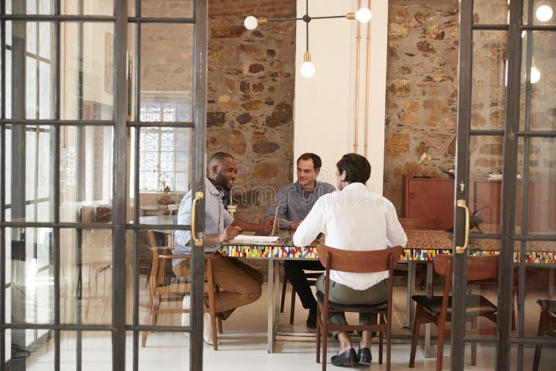 Tre unga män på ett möte i en styrelse, slut upp royaltyfria foton