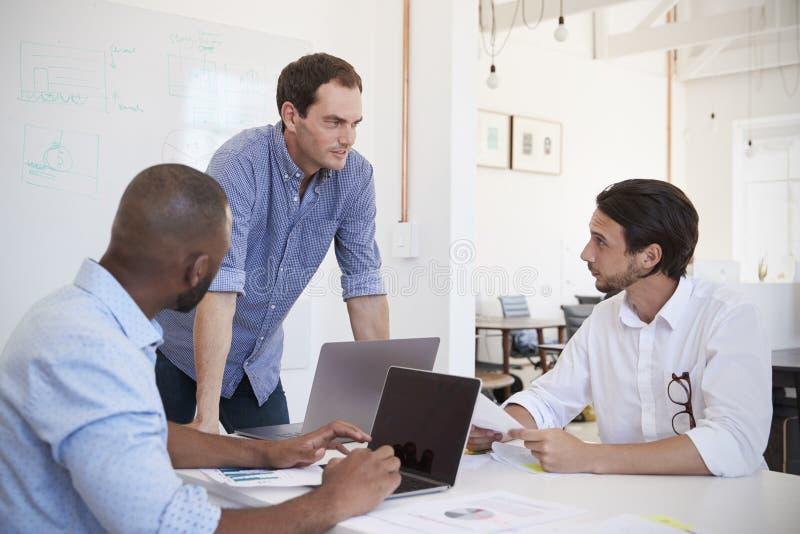 Tre unga män som diskuterar affär på ett kontorsmöte arkivbild
