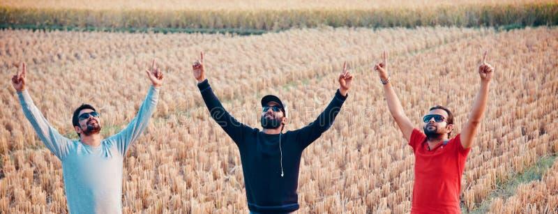 Tre unga män som lyfter händer som står i ett ställe fotografering för bildbyråer