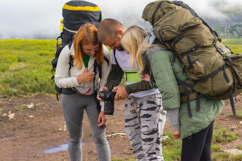 Tre unga män, turister, en grabb och två flickor på sidorna med arkivfoton