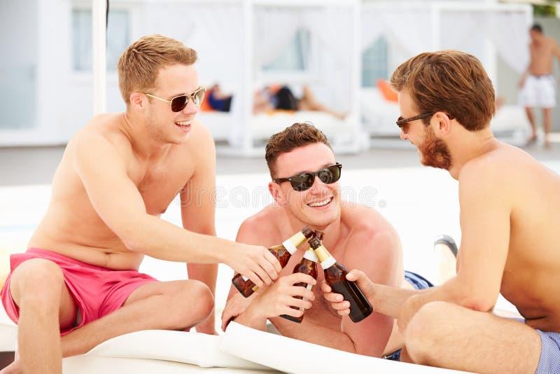 Tre unga manliga vänner på ferie vid pölen tillsammans royaltyfria bilder