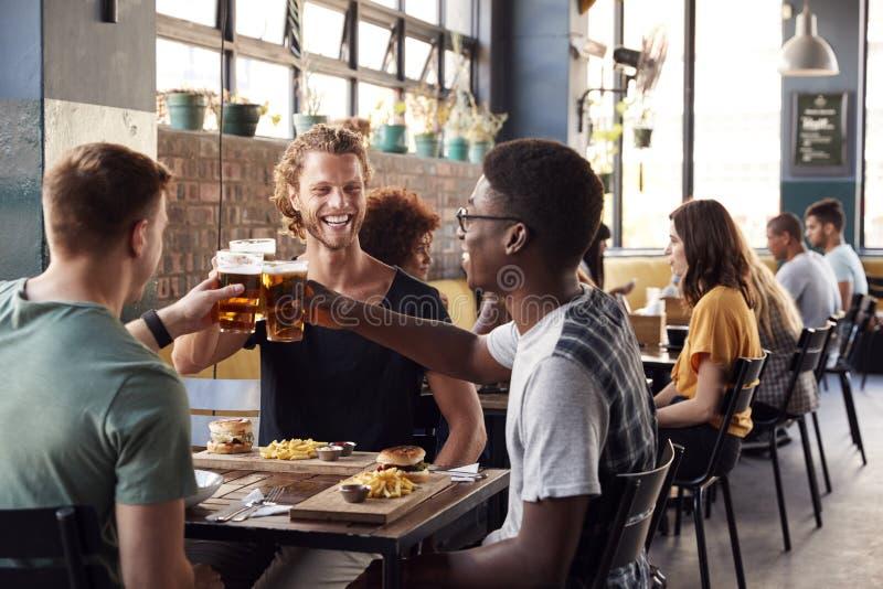 Tre unga manliga vänner som möter för drinkar och mat som gör ett rostat bröd i restaurang arkivfoton