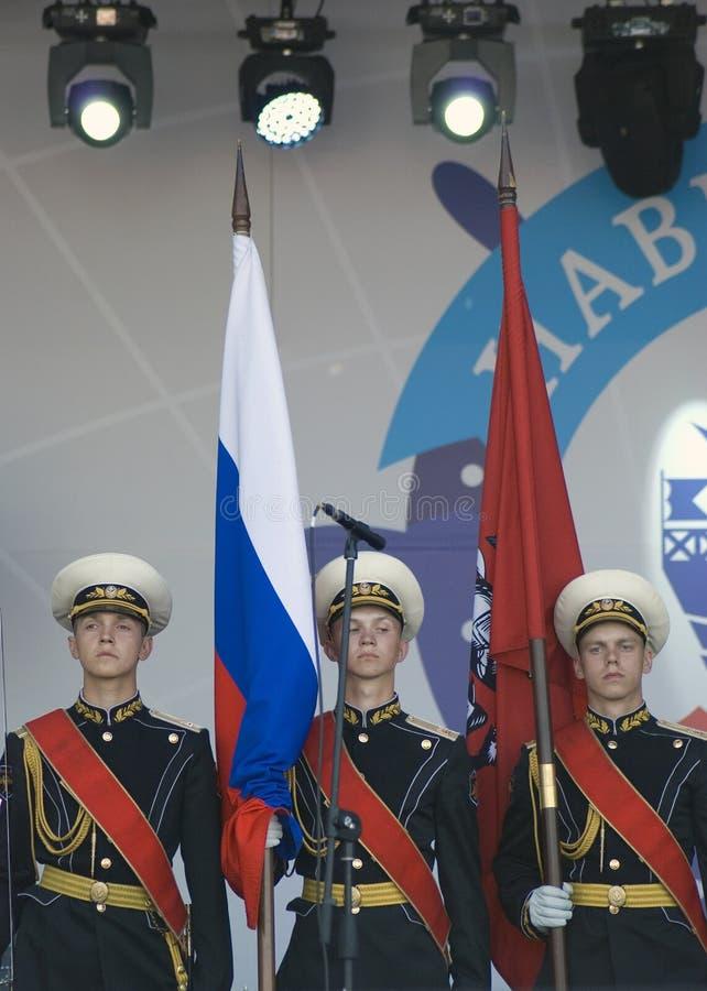 Tre unga militära män rymmer flaggor av Ryssland och Moskva arkivfoto