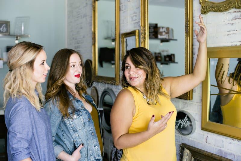 Tre unga Millennial kvinnliga händelsestadsplanerare diskuterar på ett möte arkivbild