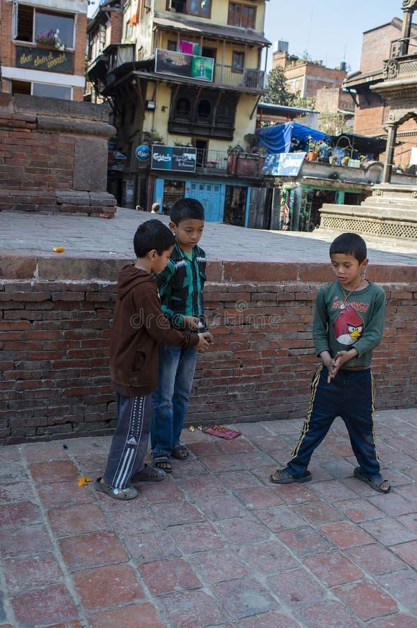Tre unga pojkar som spelar en lek med ett mynt i gatan, Katmandu, Nepal, mars 2014 royaltyfri bild