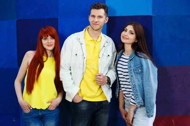 Tre unga stilfulla vänner som uppemot står ljus bakgrund royaltyfria foton