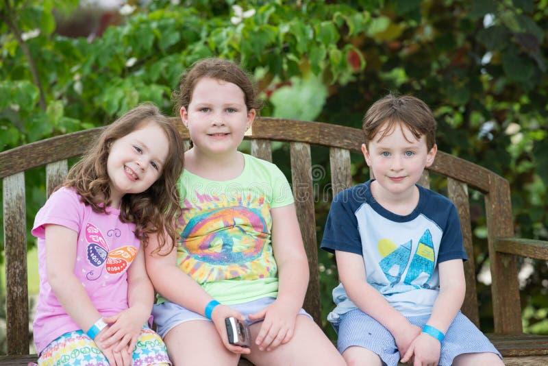 Tre unga syskon som utomhus sitter på bänk royaltyfria bilder