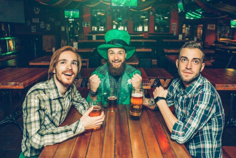 Tre unga upphetsade män som hurrar på tabellen i bar De ser upp framåtriktat och leendet Grabb på mellersta kläderSts Patrick drä fotografering för bildbyråer