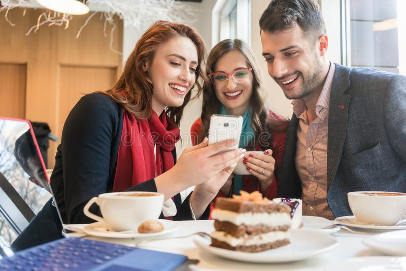 Tre unga vänner som använder en mobiltelefon för gyckel under ett kaffeavbrott royaltyfri fotografi