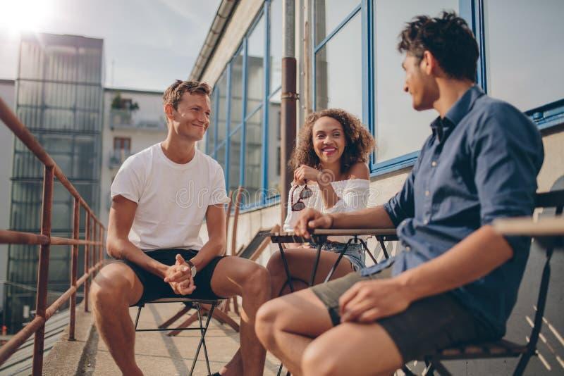 Tre unga vänner tillsammans på det utomhus- kafét royaltyfri bild