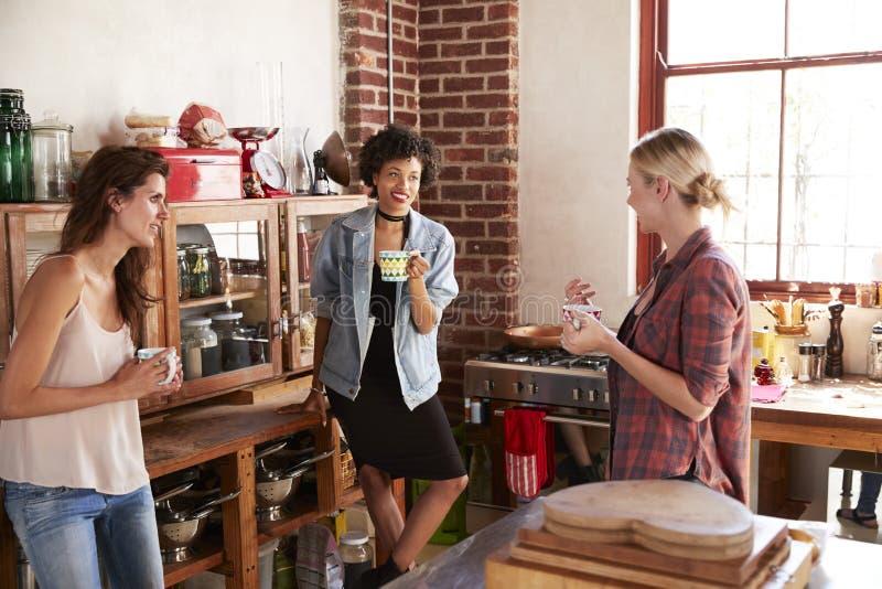 Tre unga vuxna flickvänner talar över kaffe i kök fotografering för bildbyråer
