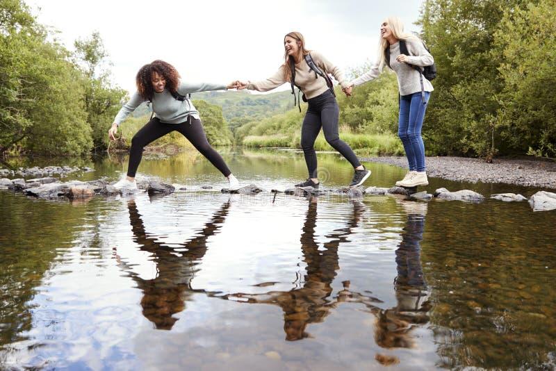 Tre unga vuxna kvinnor rymmer händer som hjälper sig, medan korsa försiktigt en ström på stenar under en vandring royaltyfria foton
