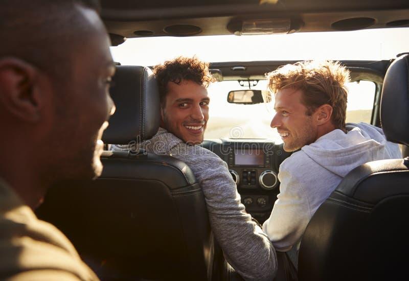 Tre unga vuxna män som kör med den öppna soltaket, tillbaka sikt arkivbild