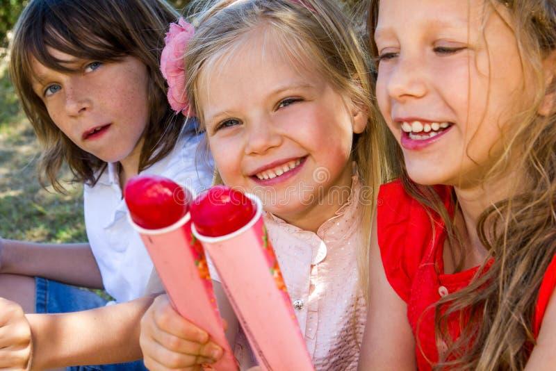 Tre ungar som äter glass. royaltyfria bilder