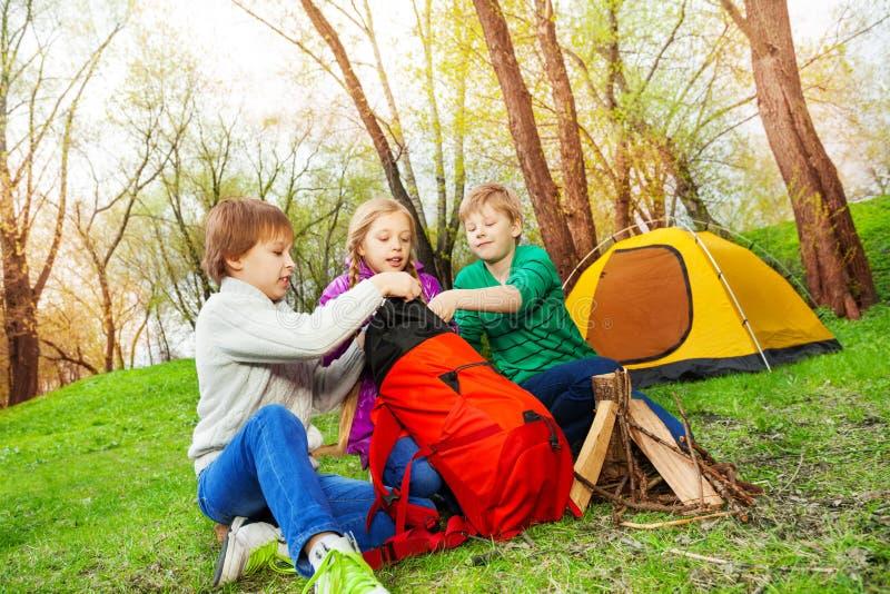 Tre ungar som packar saker in i den röda ryggsäcken royaltyfria bilder