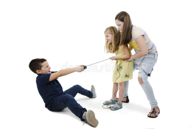 Tre ungar som slåss för videospel royaltyfria foton