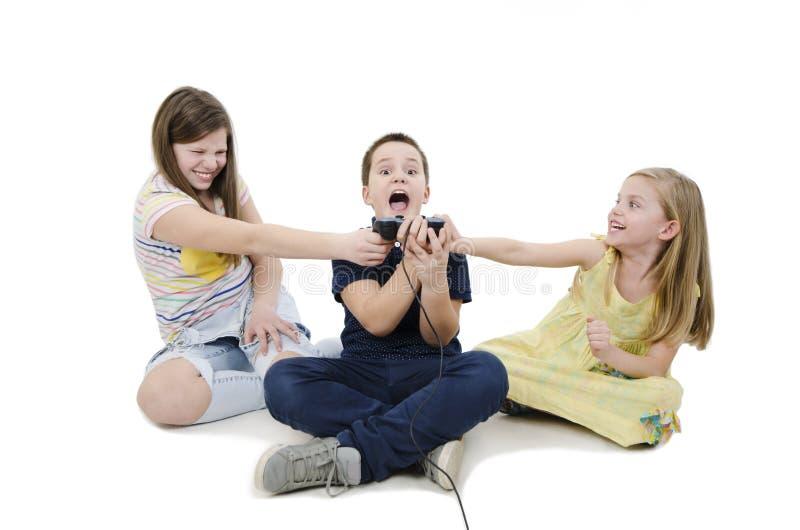 Tre ungar som slåss för videospel royaltyfri foto