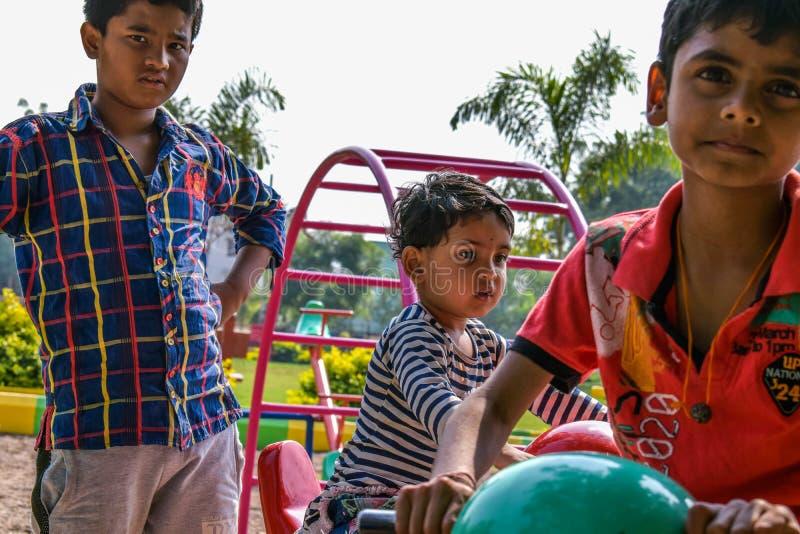 Tre ungar som spelar lekar i dagiset i ljus solig dag royaltyfri fotografi