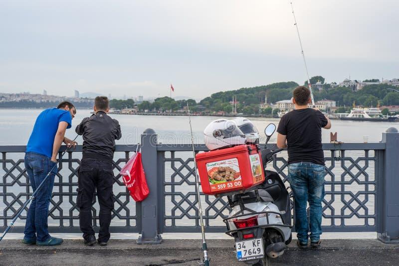 Tre uomini che pescano con tre Rohi sul ponte di Galata nel mattino in anticipo fotografie stock libere da diritti
