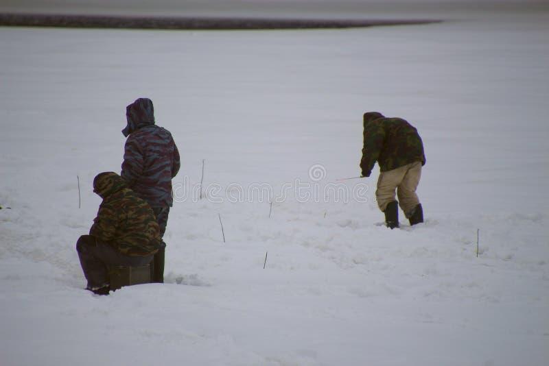 Tre uomini che pescano sul ghiaccio per pesca di inverno immagini stock libere da diritti