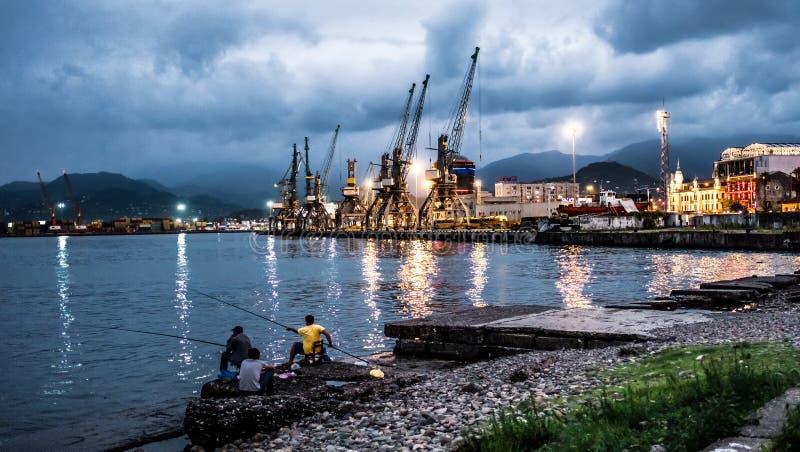 Tre uomini che pescano vicino al porto del carico fotografie stock