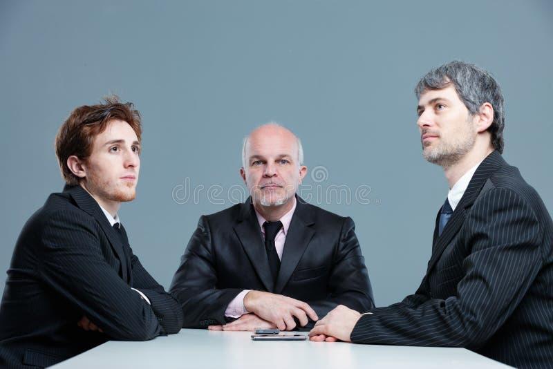 Tre uomini d'affari annoiati in una riunione immagini stock