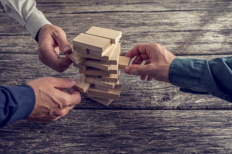 Tre uomini d'affari che giocano il gioco di legno della torre immagine stock