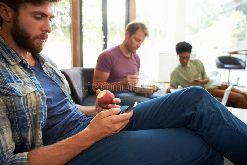 Tre uomini d'affari che hanno colazione di lavoro in ufficio immagini stock
