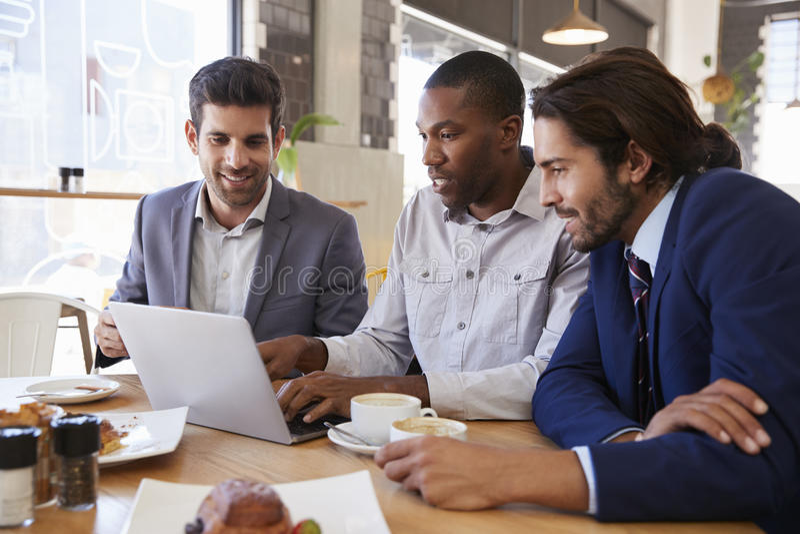Tre uomini d'affari che hanno riunione in caffetteria immagine stock