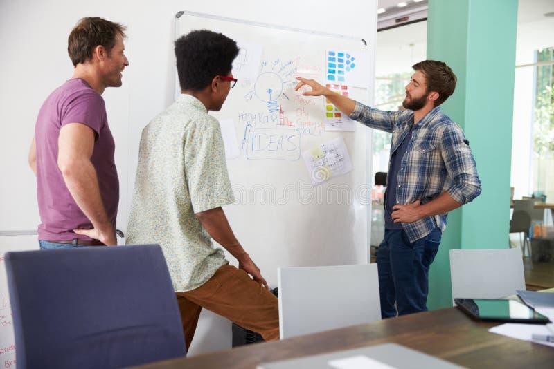Tre uomini d'affari che hanno riunione creativa in ufficio fotografia stock libera da diritti