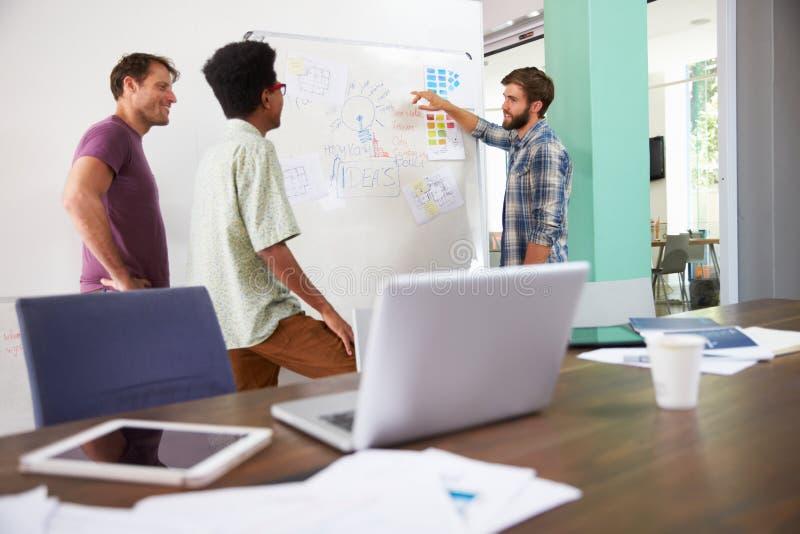 Tre uomini d'affari che hanno riunione creativa in ufficio fotografia stock