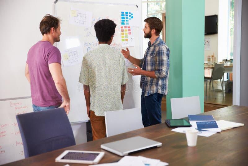 Tre uomini d'affari che hanno riunione creativa in ufficio immagine stock