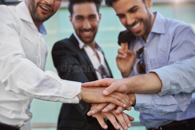 Tre uomini d'affari che si tengono per mano insieme nel gesto di unità fotografie stock libere da diritti