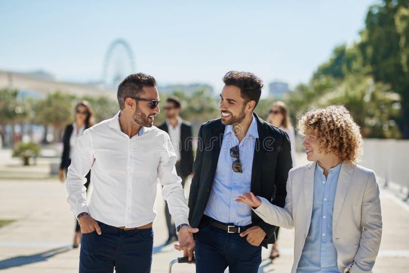 Tre uomini d'affari felici che hanno conversazione fuori fotografia stock