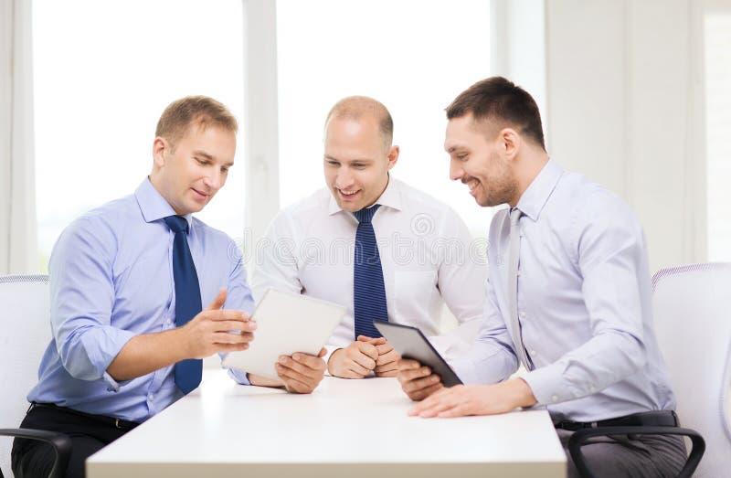 Tre uomini d'affari sorridenti con il pc della compressa in ufficio fotografia stock