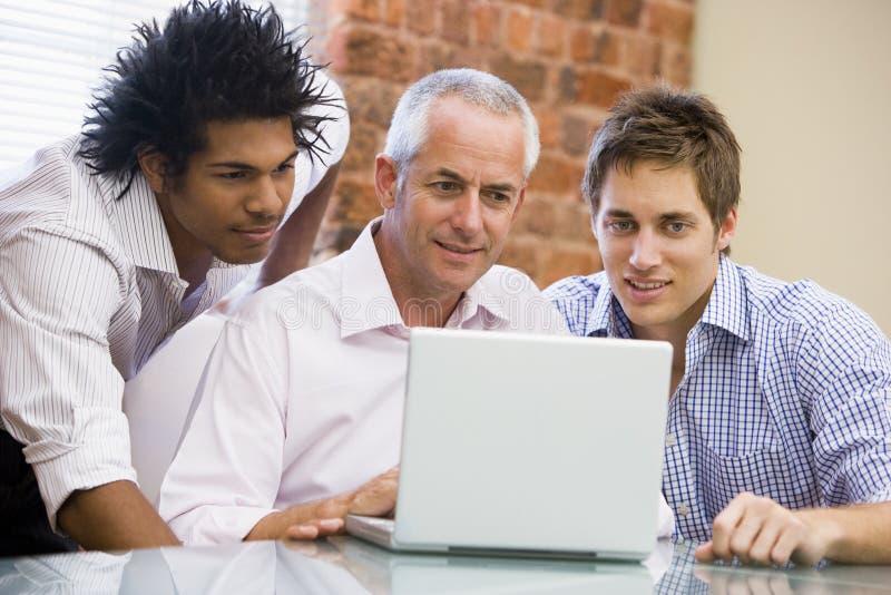 Tre uomini d'affari in ufficio che esamina computer portatile immagine stock libera da diritti