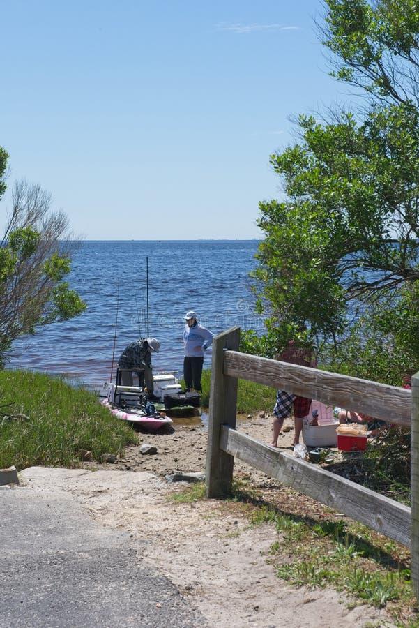 Tre uomini preparano lanciare i kajak per andare pescare lungo il fiume immagini stock